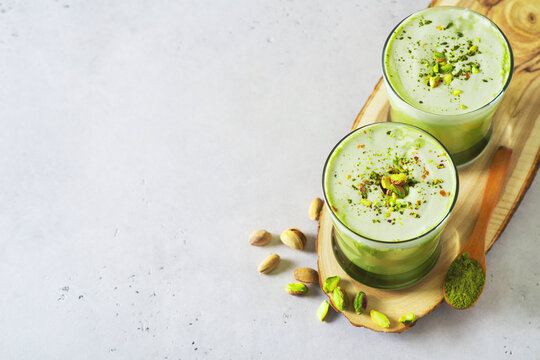 Green matcha latte with pistachios and matcha powder