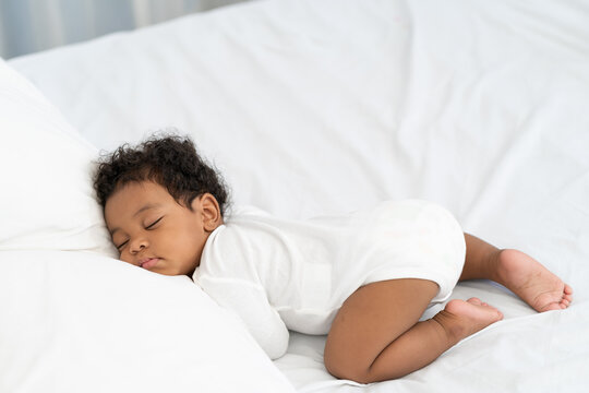 black african american baby sleeping on a white mattress.