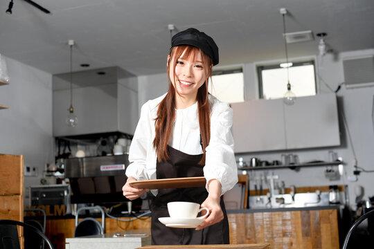 飲食店で働くエプロン姿の女性が接客するイメージ