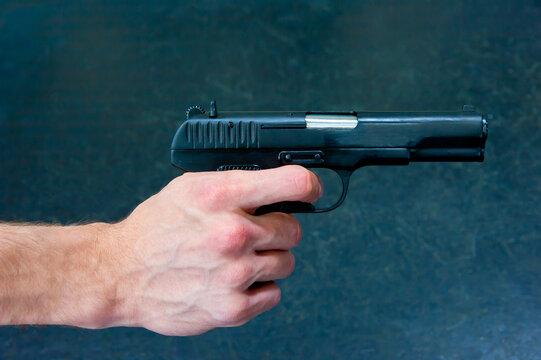 A man's hand holds a TT pistol.