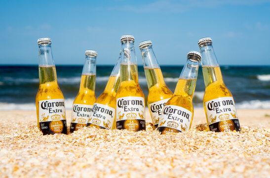 Illustrative editorial of Corona beer bottles on the beach sand: GENICHESK, UKRAINE - 19 June 2021.