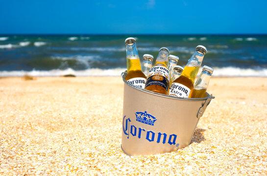 Illustrative editorial of Corona beer bottles in the branded bucket in sand: GENICHESK, UKRAINE - 19 June 2021.