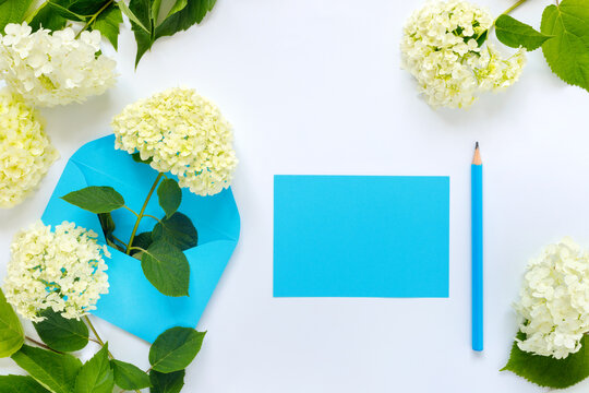 Greeting card with blue envelope, pencil and white hydrangea flowers for mother's day or birthday. Creative design with copy space for text.