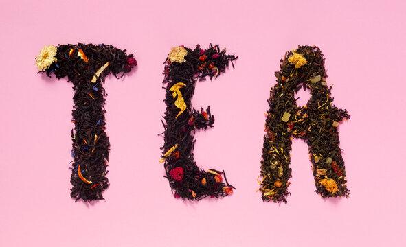 Large assortment of fruit, flower, herbal citrus teas on pink paper background