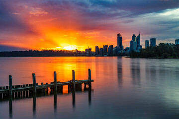 Sunset with Sunrays at Swan River, with jetty in foreground, and Perth City in background