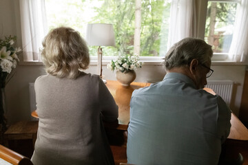 Back view of unhappy mature man and woman spouses sit separately back to back ignore avoid talking after family fight. Upset old couple have quarrel or misunderstanding. Divorce, relations concept.