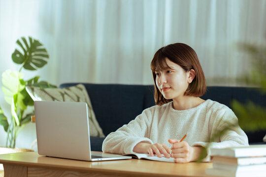 リビングでオンライン学習中の若い女性