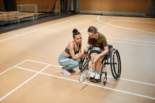 High angle view at young woman in wheelchair talking to female coach during badminton practice at sports court and using smartphone, copy space