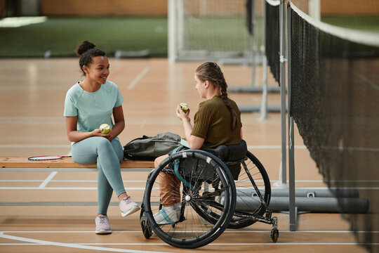 Portrait of young woman in wheelchair sharing lunch with friend at indoor sports court