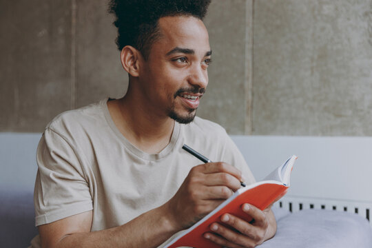Dreamful creative happy young student african american man 20s in beige t-shirt sitting on sofa indoors apartment write down memories in notebook diary, writing letter, rest on weekends stay at home