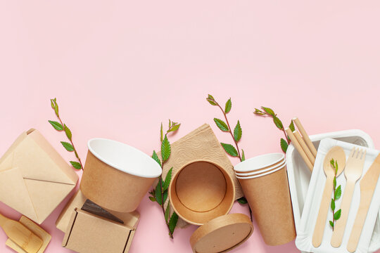 Eco craft paper tableware. Paper cups, dishes, bag, fast food containers and wooden cutlery on pink background. Recycling or zero waste concept. Top view. Copy space