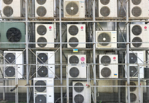 Lots of air conditioners on the wall of the building covered with the metal grid. There are LG, Daikin and Tadiran brands. KHARKIV, UKRAINE - June 17, 2021.
