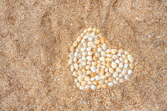 Heart symbol made with seashells on the sand. Love concept.