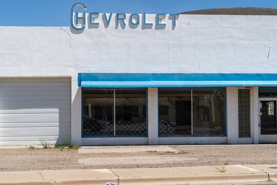 Willcox, Arizona - May 8, 2021: Old abandoned Chevrolet car dealership, with the classic logo, on a sunny day
