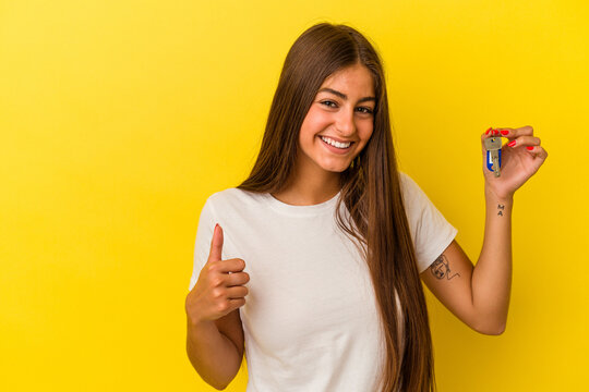 Young caucasian woman holding a home keys isolated on yellow background smiling and raising thumb up