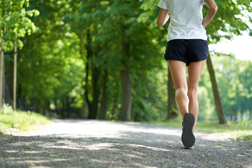 Unrecognizable woman running in the park during summer
