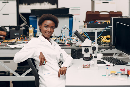 Scientist african american woman engineer working in laboratory with electronic tech instruments and microscope. Research and development of electronic devices by color black woman.