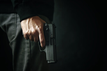 Criminal with revolver on dark background. Firearm in man's hand. Defense or attack. Murderer or armed thief. Pistol with drum. - fototapety na wymiar