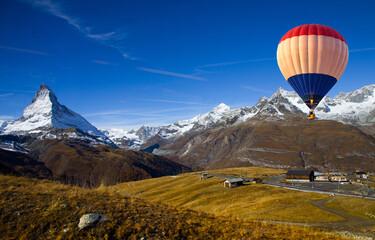 Aerial view of hot air balloon flying over Gornergrat in summer with scenic view of Matterhorn peak in background, Switzerland