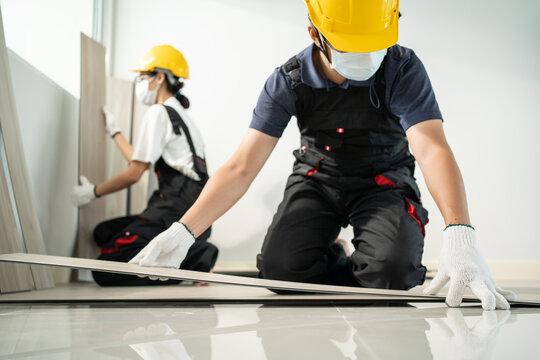 Asian Construction worker wear mask installs laminate board on floor