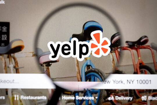 Yelp company logo on a website, seen on a computer screen through a magnifying glass.