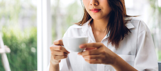 Portrait of smiling happy cheerful beautiful pretty asian woman relaxing drinking and looking at cup of hot coffee or tea.Girl felling enjoy having breakfast in holiday morning vacation at home