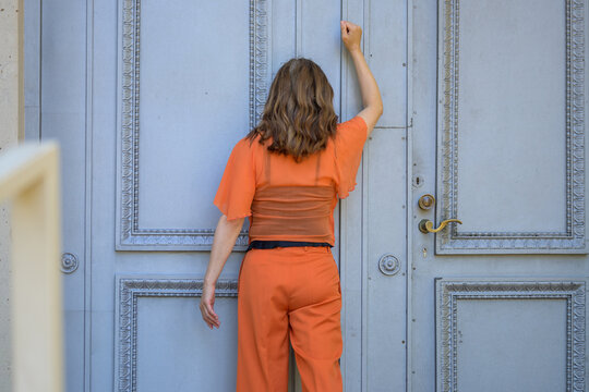 Rear view of a woman in orange knocking on a historic door