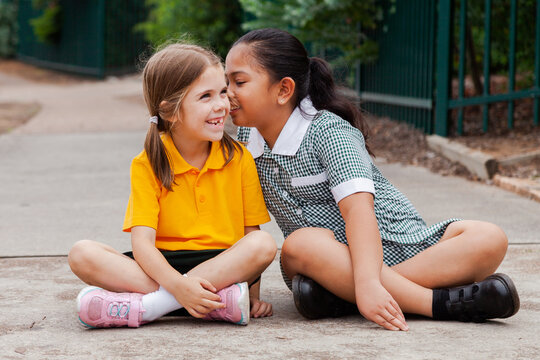 Two school girls sitting outside one child whispering secrets to other kid