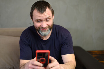 Fototapeta Portrait of adult caucasian man with beard smiling uses phone while sitting on sofa at home obraz