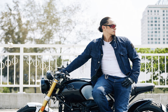 Portrait of cool stylish man in sunglasses sitting on motorcycle and looking away