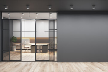 Obraz Black wall with copyspace for your text or logo next to doors to sunny office with monochrome style interior design, modern laptops on white tables and wooden floor. 3D rendering, mockup - fototapety do salonu