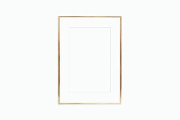 Fototapeta Thin gold frame with mat on a white wall obraz