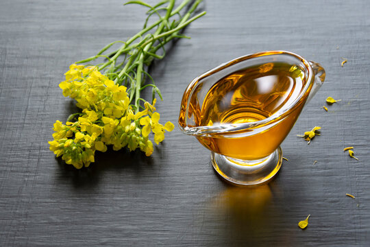 Mustard oil in a gravy boat and mustard flowers on a dark background