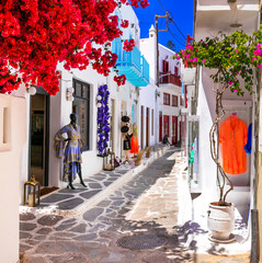 Authentic traditional Greece. Charming colorful floral streets of Mykonos island with fashion shops. Cyclades