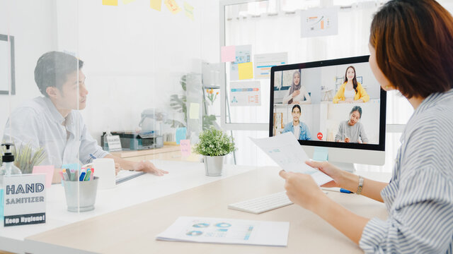 Asia businesspeople using desktop talk to colleagues discussing business brainstorm about plan in video call meeting in new normal office. Lifestyle social distancing and work after corona virus.