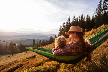 Boy with mom resting in a hammock in the mountains at sunset