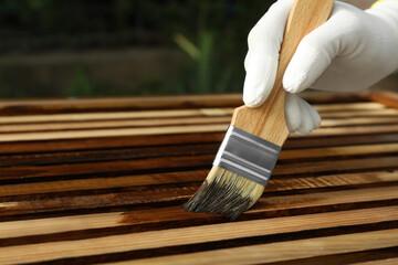 Obraz Worker applying wood stain onto planks outdoors, closeup - fototapety do salonu