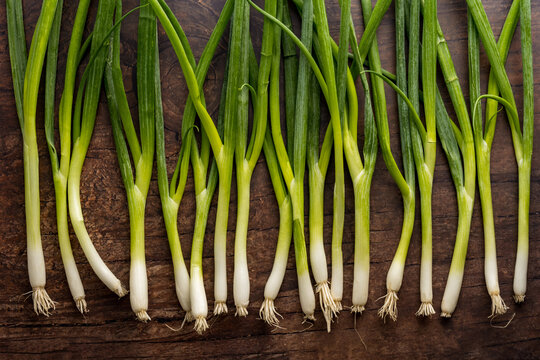 Green onions arranged on a wooden surface