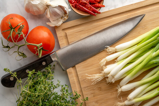 Knife on cutting board with onions tomatoes and spices