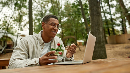Smiling young african american man eating fresh salad
