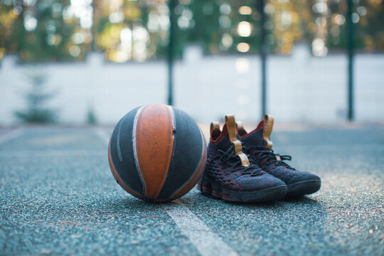 Basketball ball, sportive shoes for workout on basketball court, close up advertising photography in sunny day