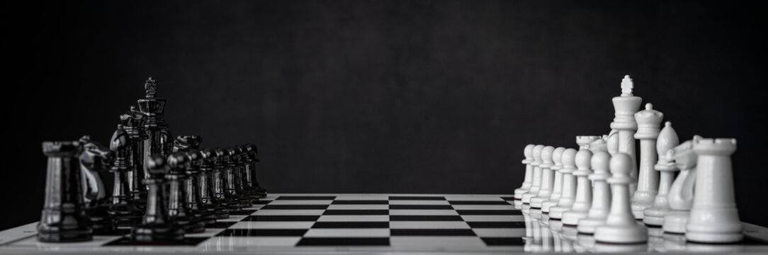 Chess pieces are arranged on a chessboard. The beginning of a chess game. Chess as a symbol of leadership, struggle, victory, strategy, business. Retro style.