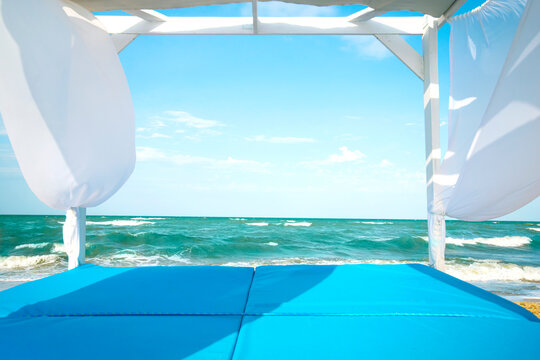 Beatiful sea beach scene with blue canopy and white curtain for luxury summer relaxation. Summer vacation or holiday background with copy space.