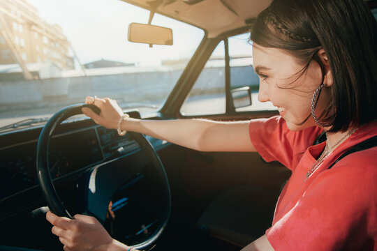 Girl wearing stylish outfit sitting behind the wheel in the driver's seat