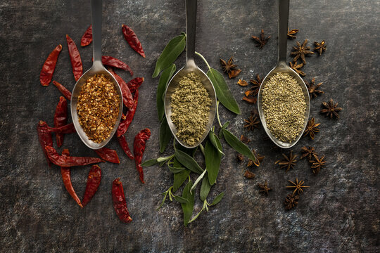 Chili pepper sage and star anise on metal spoons, ground and whole spices