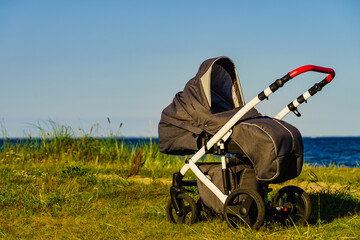 Baby stroller outdoors on seashore.