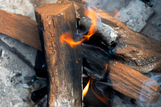 Photo of a fire pit and fire consisting of mesquite dried-wood logs and fruit wood charcoal on a sunny day of June 20, 2021.