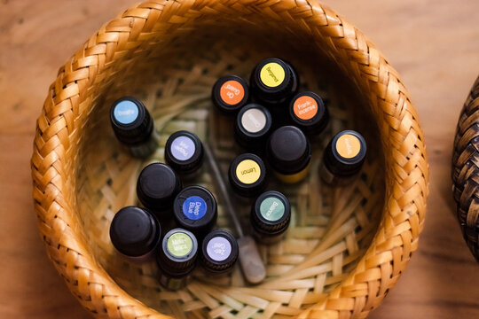 mall glasses of essential oils in straw bowl top view