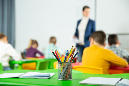 Stand with colored pencils and notebooks on the desk against the background of elementary school students