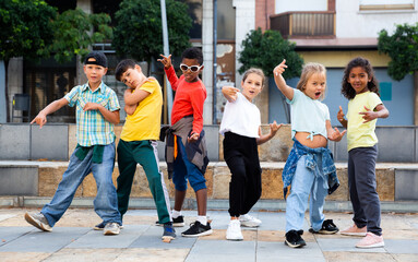 Group of children in casual clothes training hip-hop on street, learning modern dance movements